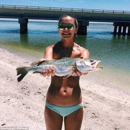 比基尼美女以鱼遮胸秀性感