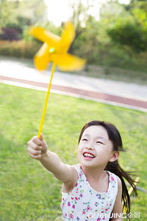 ...的小女孩拿着纸风车玩