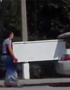 女大力士 哈男子开车女友在车后托冰箱