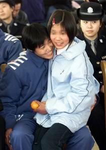 北京市女子监狱里的女犯魏云娥(左)高兴地搂着13岁的女儿李晶晶....