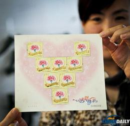 ...工作人员展示《感恩母亲》邮票小版.该套邮票图案采用了一枚粉...