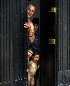 黎巴嫩的一个家庭,大人带着小孩从门缝中窥视着远处的难民营-法新...