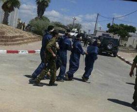 一名持枪军人正押送4名被蒙上眼睛戴着镣铐的武装人员.-疑似哈马斯...